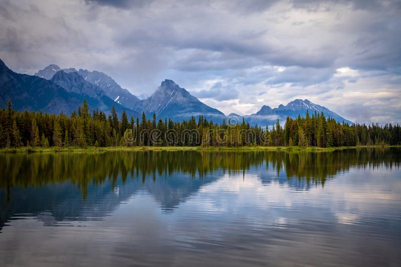 Mountains reflecting in the calm waters of Spillway Lake in Peter Lougheed Provincial Park, Alberta stock photos