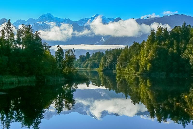 Mountains reflecting in the water of Lake Matheson, New Zealand. Lake Matheson early in the morning, reflection of mountains, clouds and trees in the blue water royalty free stock photography