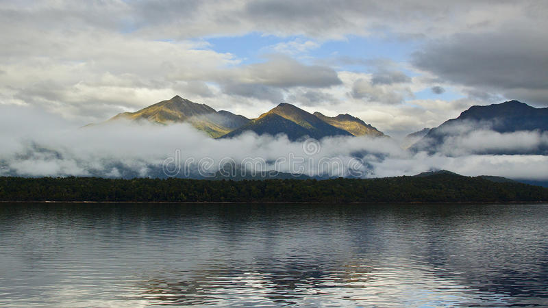 Mountains rising above the clouds stock photo