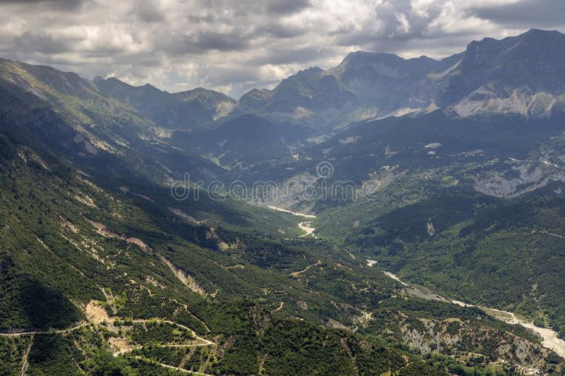 The mountains and the river Kalarrytikos Greeceon a cloudy day royalty free stock image