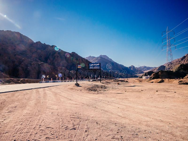 Mountains and road in desert near Dahab. Mountains, road and sand in desert near Dahab, Egypt. Sun flares stock photography