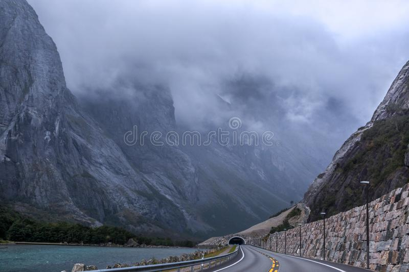Mountains road with tunnel near Ã…ndalsnes and Trollstigen in Norway, rocky hills and river, scenic. And epic nature valley with clouds view. Traveling by stock photography