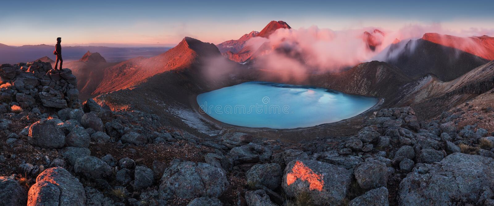 Mountains and silhouette of standing man. Early morning sunrise, landscape scenery of blue lake, wild mountains and huge volcano. stock photo