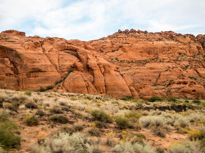Mountains of Snow Canyon. Red rock mountains and green shrubs cover Snow Canyon state park in St. George, Utah royalty free stock image