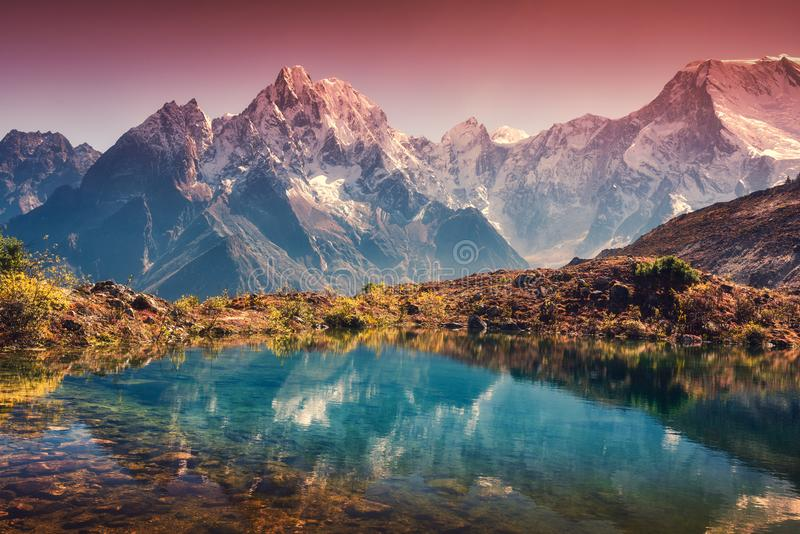Mountains with snow covered peaks, red sky reflected in lake stock photography