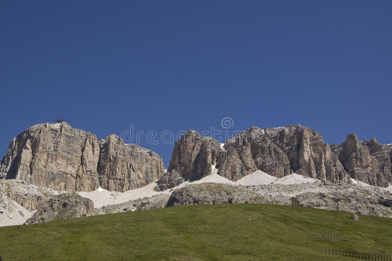 Mountains, snow and grass. Dolomites alps in trentino during the summertim in italy stock photo