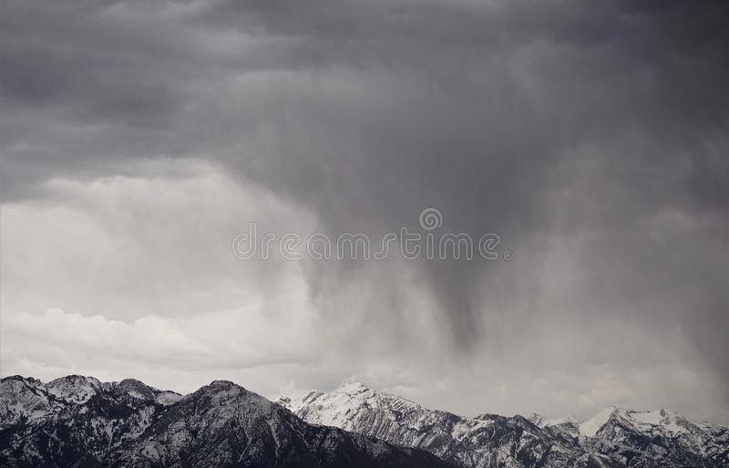 Mountains in snow and rain. Cloudburst of rain falls on the snow covered Wasatch Mountains of Utah in the American Southwest.  Black and white contrast of the stock images