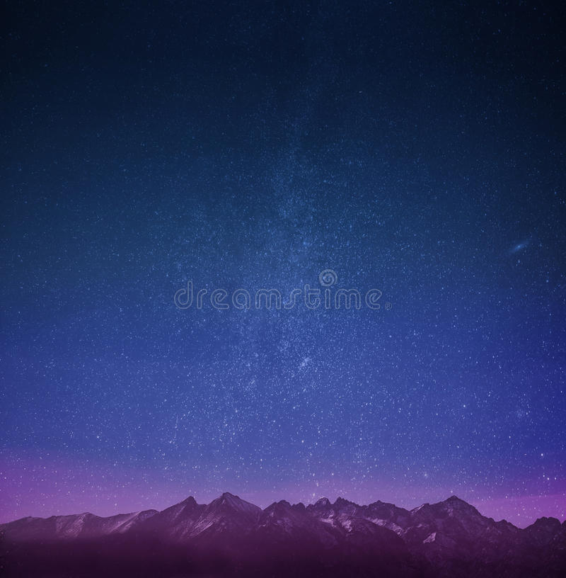 Mountains with stars wallpaper. With purple tint stock image