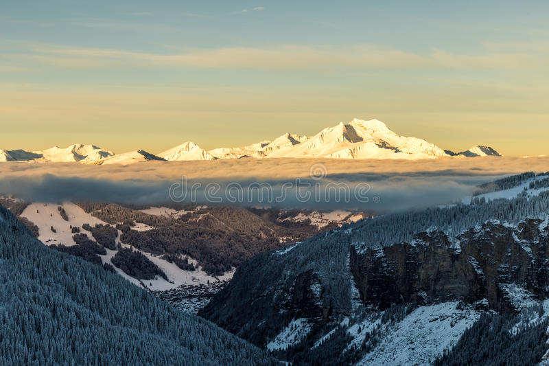 Mountains with a sunrise surrounded by clouds royalty free stock photos