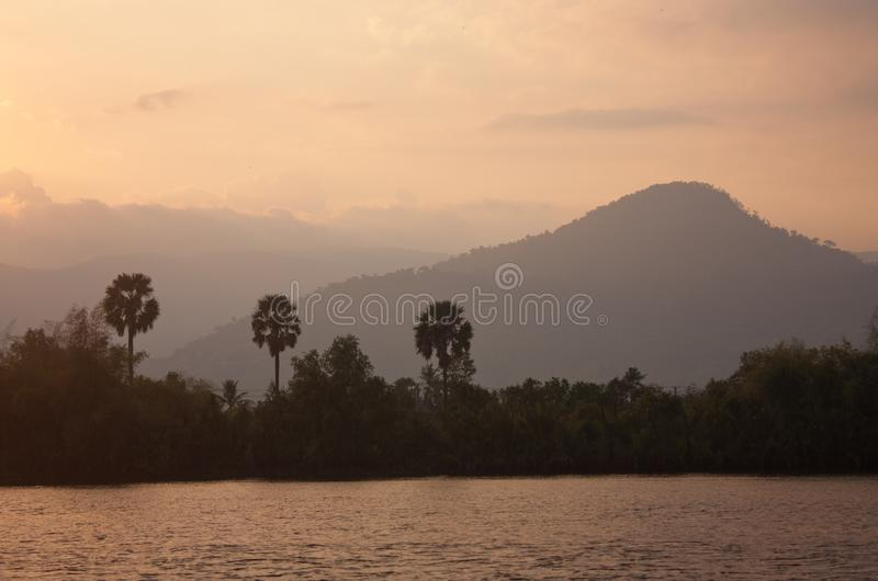 Mountains during a sunset as seen from the Preaek Tuek Chhu River near Kampot in Cambodia. In SE Asia, adventure, asian, beautiful, boat, calm, chill, cloud stock photo