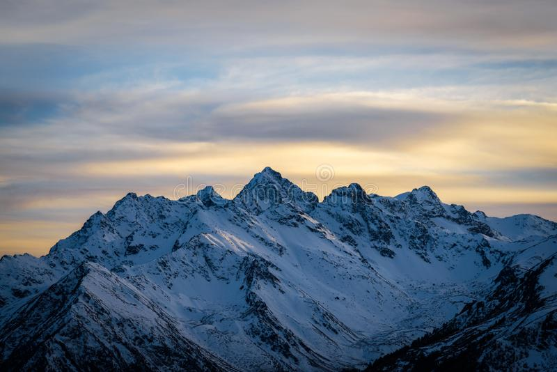 Mountains after sunset. Snowy mountain range immediately after sunset. In the sky a little cloudy. The concept of extreme hiking and conquering mountain peaks royalty free stock photo