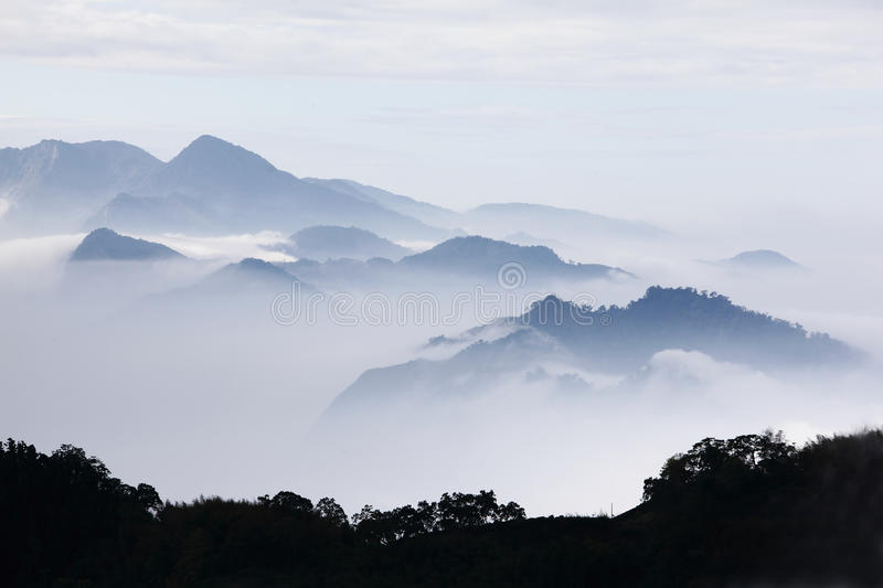 Mountains with trees and fog in monochrome color stock photography