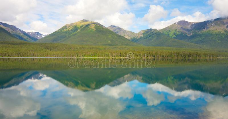 Mountains and trees reflected in a calm lake along the cassiar highway. A lovely scenic spot in the rockies as seen in northern british columbia in the royalty free stock photography