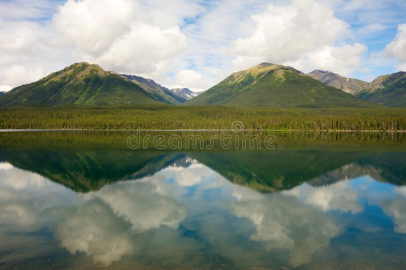 Mountains and trees reflected in a calm lake along the cassiar highway. A lovely scenic spot in the rockies as seen in northern british columbia in the stock images