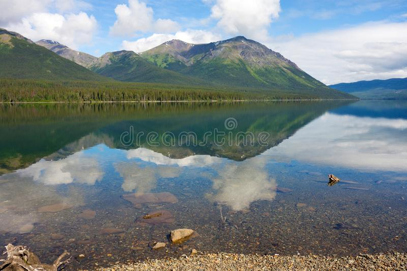 Mountains and trees reflected in a calm lake along the cassiar highway. A lovely scenic spot in the rockies as seen in northern british columbia in the royalty free stock image