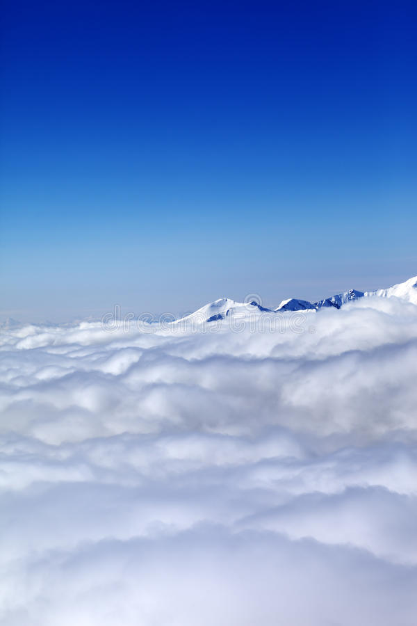 Mountains under clouds and clear blue sky. Caucasus Mountains, Georgia, Gudauri. View from ski slope royalty free stock photography
