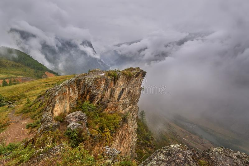 Mountains valley fog river clouds. Scenic top view on the mountains, the valley and the winding river in thick fog and clouds stock photo