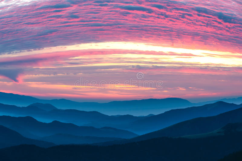 Mountains View many stacked foggy ranges and purple Clouds royalty free stock photography