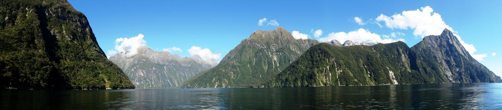 Mountains and water. Mountains meet the sea in the Fiord of Milford Sound, New Zealand stock image