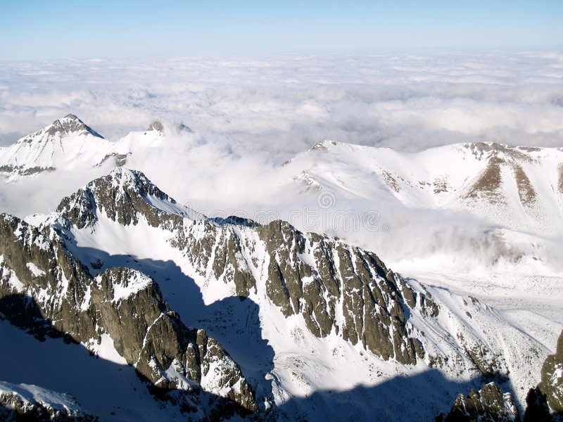 Mountains in winter. High angle view over looking snow capped peaks of High Tatra mountains obscured with cloudscape, Slovakia royalty free stock photography