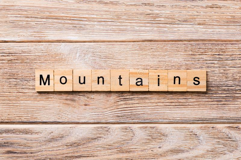 Mountains word written on wood block. mountains text on wooden table for your desing, concept stock image
