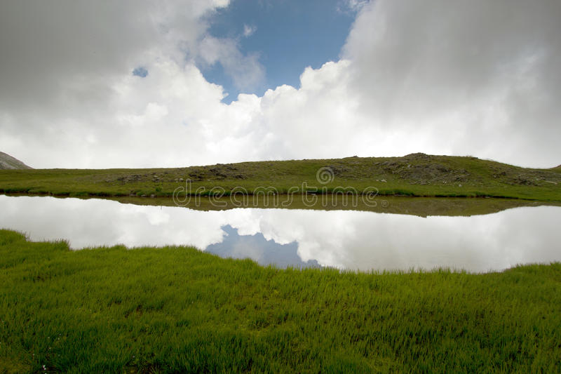 Mountainsee mit symmetrischer Reflexion der Wolken lizenzfreies stockfoto