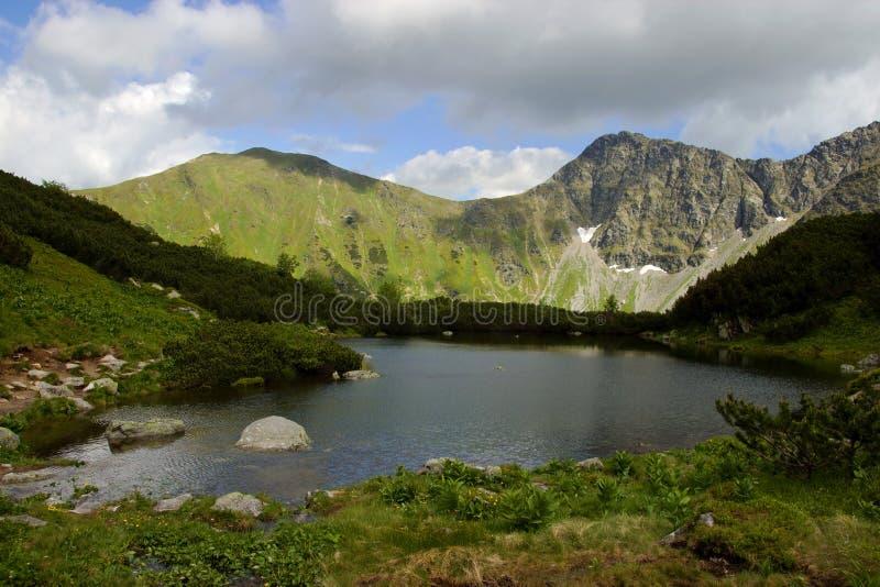 Mountainsee umgeben durch Hügel lizenzfreie stockfotografie