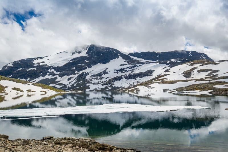 Mountainsee und schneebedeckte Felsen, Norwegen stockbild