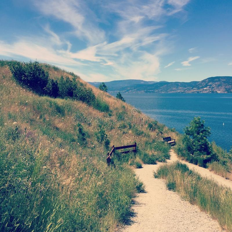 Mountainside hiking trail with bench and lake view. Hiking trail on mountainside with wooden fence and bench overlooking lake and mountains royalty free stock photography