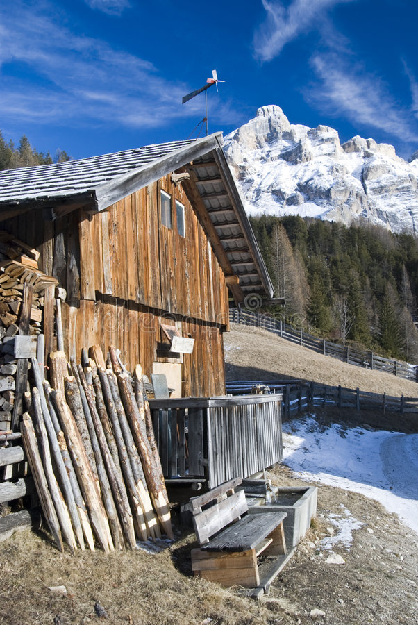 Mountainside house. House on a rural mountainside with snow-covered mountain in the background stock photography
