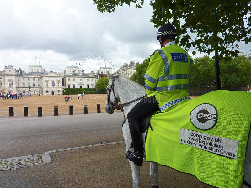 Mounted Police. London Child Protection. A mounted Policeman overlooking Horse guards Parade at Whitehall in London. The London Eye is in the background showing stock photography