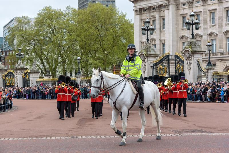 Mounted police officer leads marching Royal Guard soldiers royalty free stock photo