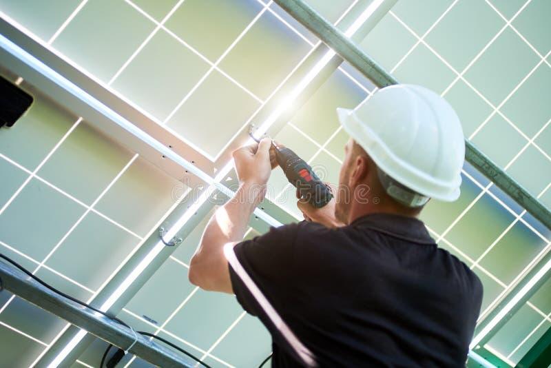 Mounter που φορά το άσπρο κράνος που λειτουργεί με το τρυπάνι που εγκαθιστά τα ηλιακά πλαίσια στοκ φωτογραφίες