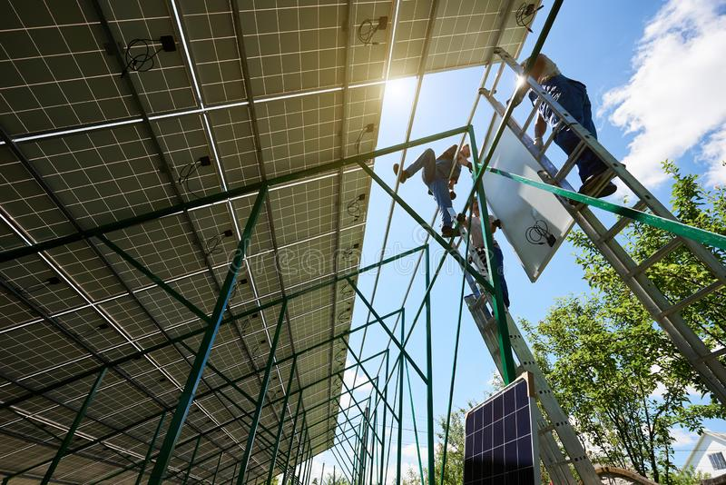 Mounters team installing solar batteries on house`s roof. royalty free stock image