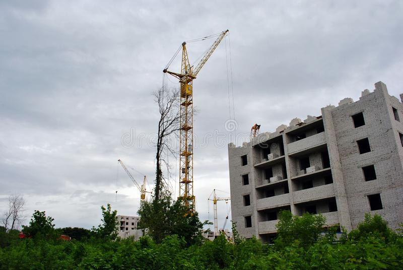 Mounting crane at construction of apartment building, green trees in the foreground, horizontal composition, cloudy rainy sky royalty free stock photo