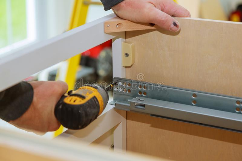 Mounting furniture with screwdriver fixing cabinet drawers hinge adjustment on kitchen cabinets. Mounting furniture with screwdriver fixing cabinet drawers hinge royalty free stock photos