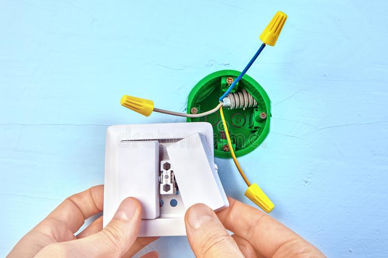 Mounting of two-button light switch. Electrician is installing european standart socket box, electric installation work. Double switch placed in the socket stock image