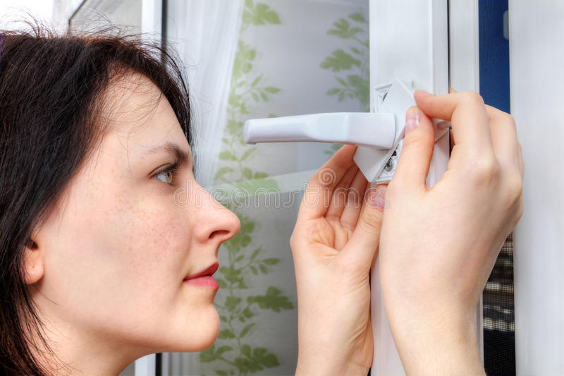 She mounts the restrictor opening windows on plastic frame, close-up. Young woman sets the limiter of opening the window on a plastic frame, close-up stock images