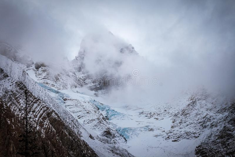 A mountsain in the Canadian Rocky Mountains shrouded in clouds on a cold day stock image