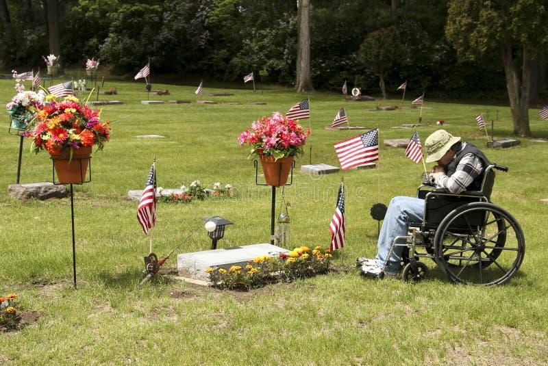 Mourning at a graveside. Disabled senior vet mourning at a graveside stock photo