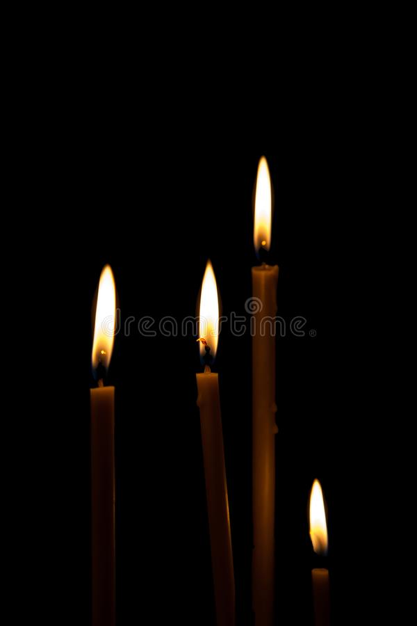 Mourning Remembrance day memorial funeral peace crematorium condolence concept. Close up Portrait vertical four burning fired can. Dles isolated with orange stock photography