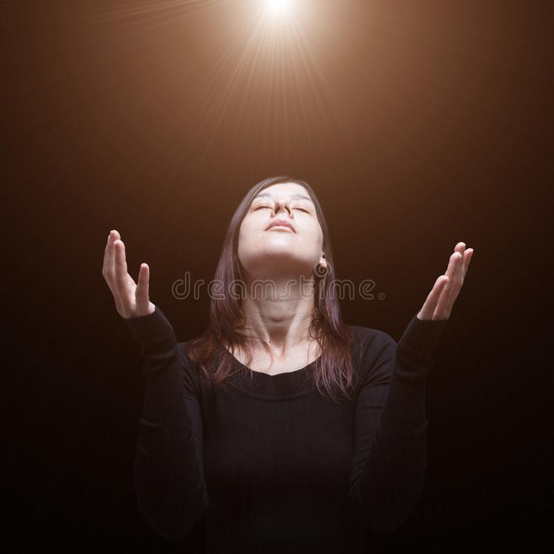 Mourning woman praying, with arms outstretched in worship to god royalty free stock photography