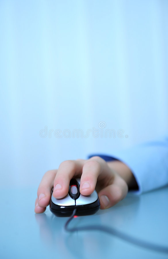 Mouse click. Close up of hand clicking computer mouse on desk stock image