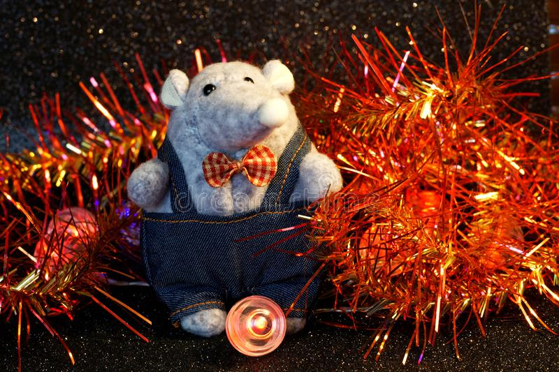 A mouse next to New Year tinsel and LED lights. A symbol of wealth, wealth and 2020 on the Chinese calendar. Night magic. Soft toy stock photography