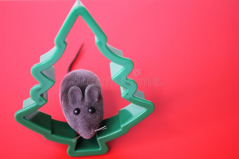 Mouse is a Symbol of new year 2020. Toy mouse and the figure of a Christmas tree on a red background. New year and Christmas concept. Copy space royalty free stock images