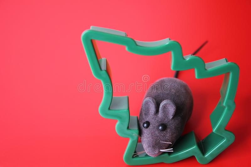 Mouse is a Symbol of new year 2020. Toy mouse and the figure of a Christmas tree on a red background. New year and Christmas concept. Copy space stock images