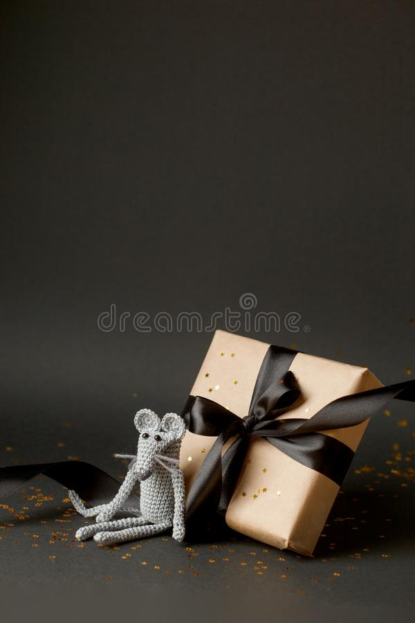 Mouse is a Symbol of new year 2020. Toy mouse and stylish gift box with black bow on black background. New year and Christmas. Concept. Copy space. Vetical stock photo