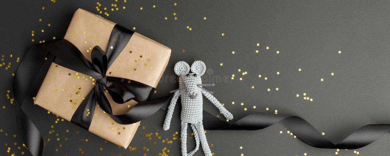 Mouse is a Symbol of new year 2020. Toy mouse and stylish gift box with black bow on black background. New year and Christmas. Concept. Copy space. Banner stock images