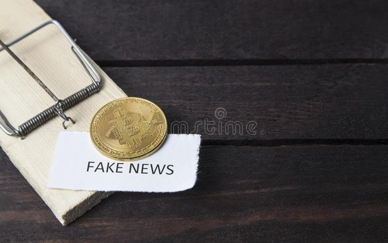 Mouse trap, bitcoin and the word: fake news. stock photography