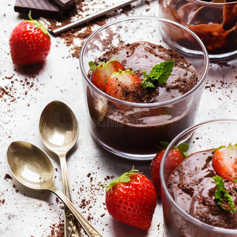 Mousse de chocolate con las fresas en vidrio en la tabla rústica imagenes de archivo